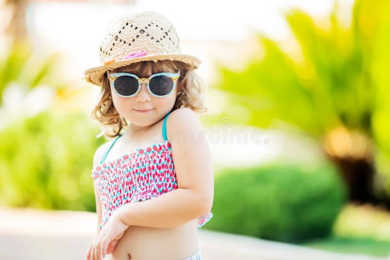 W górę portreta urocza mała dziewczynka przy tropikalnym kurortem, drzewka palmowe przy tłem, pogodny letni dzień zdjęcia stock