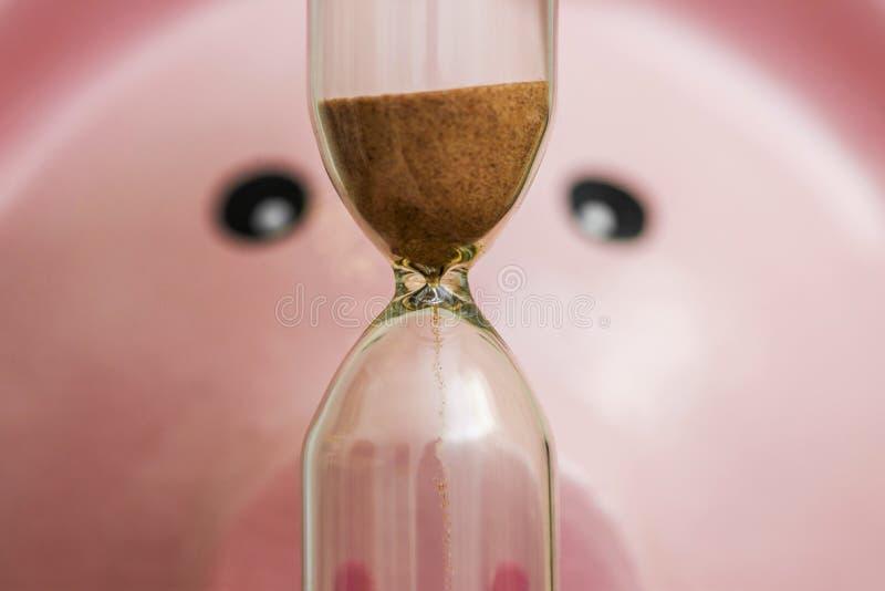 W górę różowego porcelany prosiątka banka patrzeje hourglass Pojęcie oszczędzanie pieniądze i przelotny czas zdjęcia royalty free