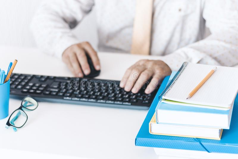 W górę ręka w średnim wieku mężczyzny pisać na maszynie na klawiaturowym laptopie w białej koszula i żółtym krawacie, plastikowy  zdjęcie royalty free