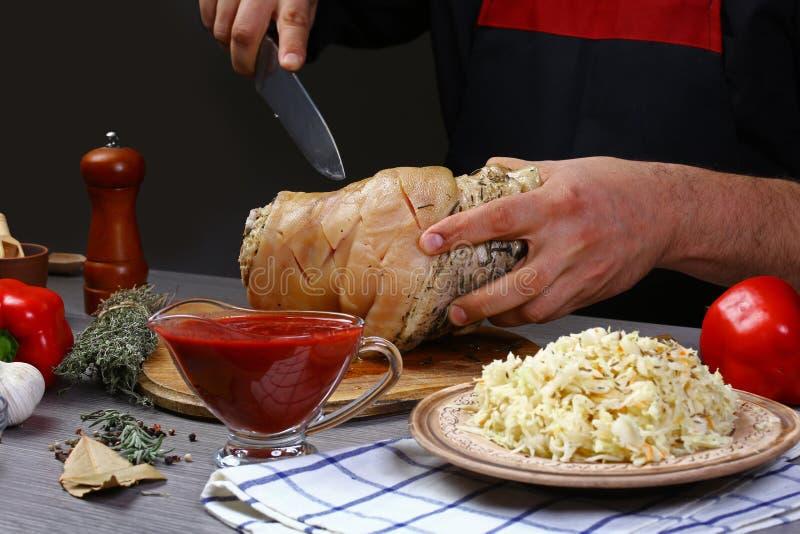 W górę ręki szef kuchni wieprzowiny kulinarny knykieć na Kulinarny tło fotografia stock