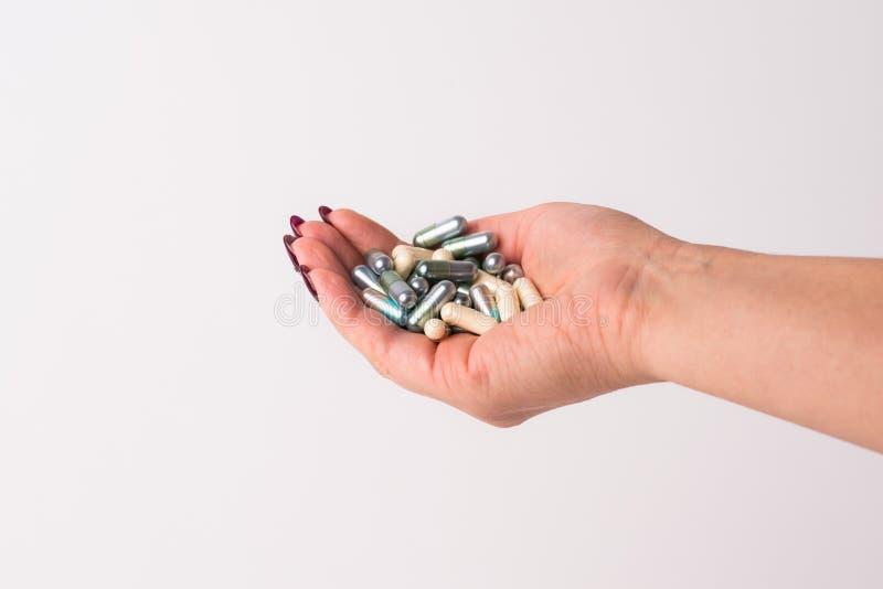 W górę ręki trzyma różnorodne kapsuły i medycyny Bia?y odosobniony t?o zdjęcie stock