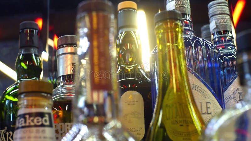 W górę rozmaitości alkohol w barze Rama Kolorowy szklanych butelek stojak na barze odpierającym na tle jaskrawe lampy zdjęcie stock