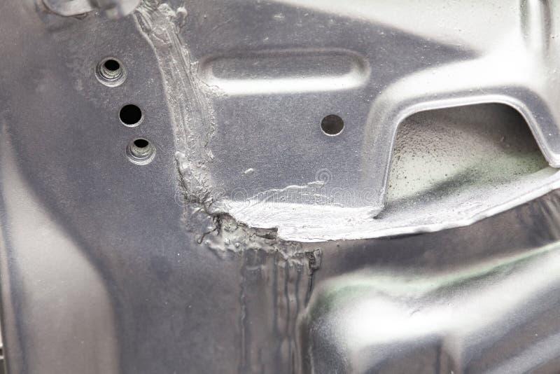 W górę spawki łączy kruszcowe części samochód mażący z sealant i malujący srebny kolor na metalworking obrazy royalty free