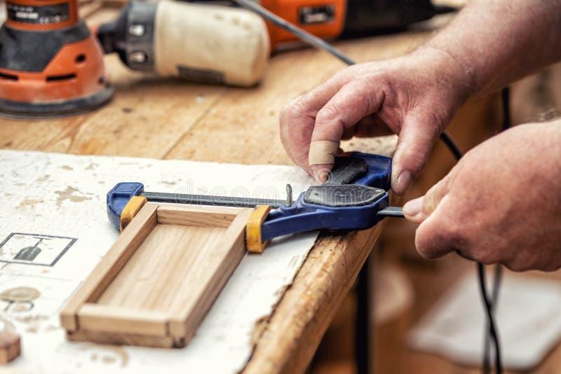 W górę starszego cieśli klei drewnianą rzemiosło powierzchnię i łączy z kahatami Woodwork cieśla z wyposażeniem i narzędziami prz zdjęcie stock