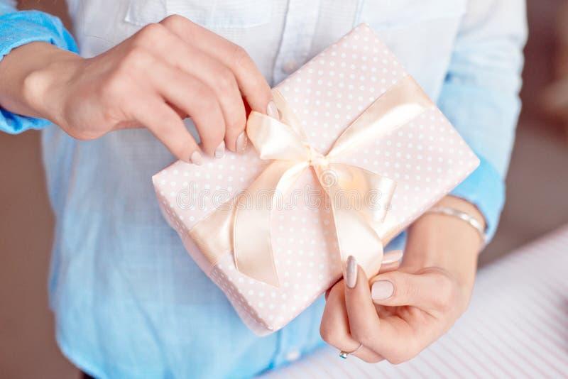 W górę strzału żeńskie ręki trzyma małego prezent zawijający z różowym faborkiem Mały prezent w rękach kobieta salowa obraz royalty free