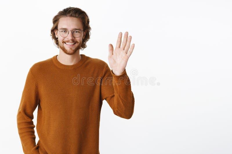 W górę strzału powabny życzliwy mężczyzna mówi jako falowanie z nastroszonej palmy i uśmiechniętego spotkania ono uśmiecha się no fotografia stock
