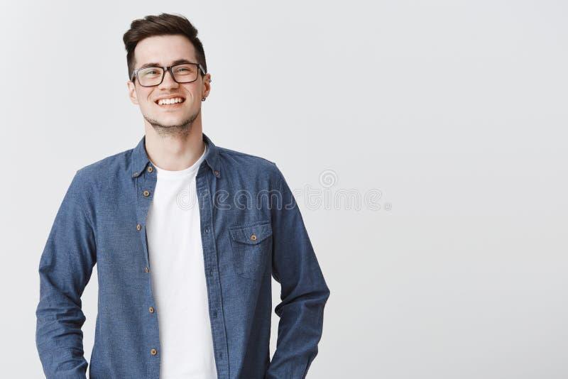 W górę strzału szczęśliwy przyglądający przystojny młody mądrze męski coworker w szkłach i błękitnej koszulowej uśmiechniętej poz obrazy stock