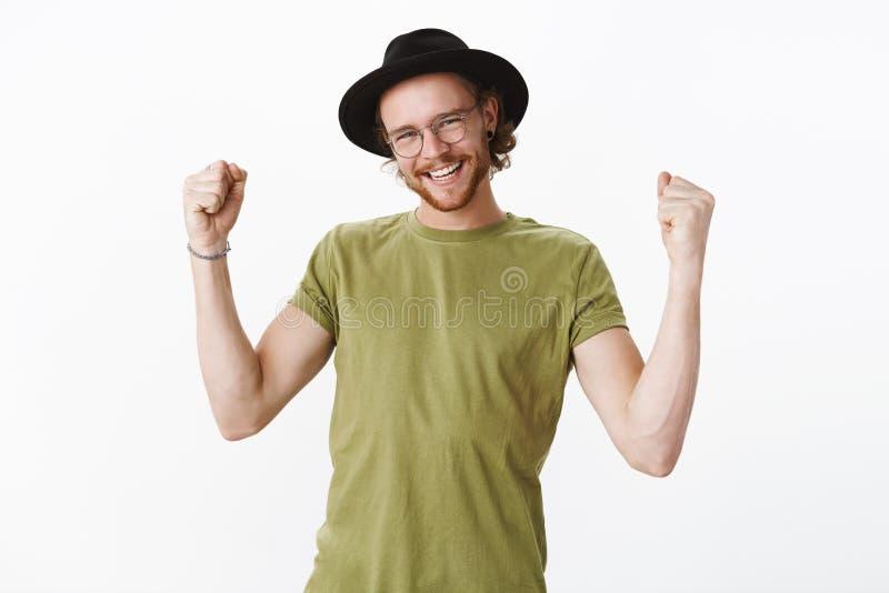 W górę strzału zadowolona pomyślna samiec w szkłach i kapeluszowy wrzeszczeć tak dumnie jako zaciskać nastroszone pięści w zwycię obrazy stock