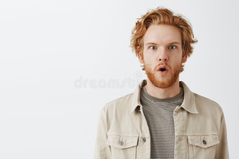 W górę strzału zainteresowany i imponujący przystojny zadziwiający rudzielec facet z brodą wewnątrz w kurtce nad koszulki falcowa obrazy stock