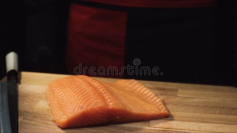 W górę surowego łososia polędwicowego na drewnianej desce z nożem Widok soczysty kawałek łosoś przed ciąć przygotowywać fotografia royalty free