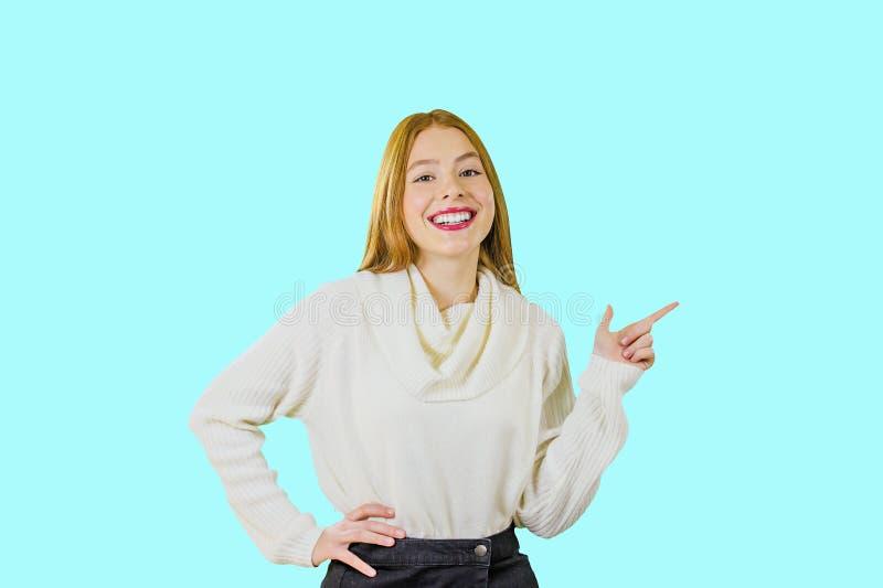 W górę szczęśliwej miedzianowłosej dziewczyny pokazuje kierunek z palcem wskazującym Jaskrawy studio strzelający modna młoda dzie fotografia royalty free