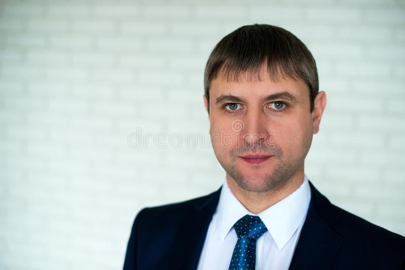 W górę twarz portreta mężczyzna w krawacie i garniturze, stoi przed białym ściany z cegieł tłem obraz stock