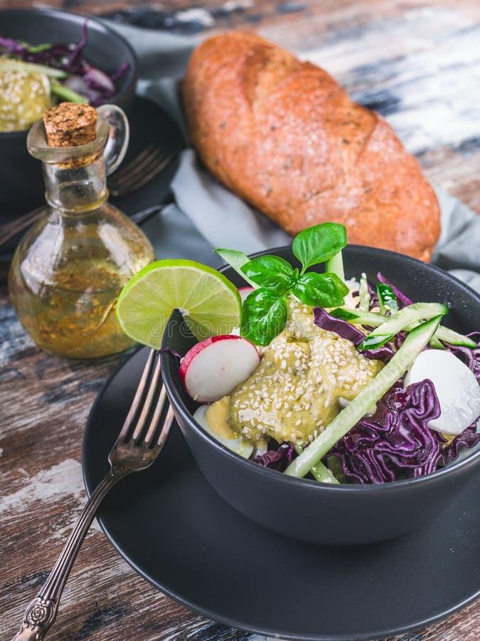 w górę Włoskiego ciabatta, oliwy z oliwek i świeżego warzywa sałatka w ciemnym pucharze Sałatka z rzodkwią, czerwona kapusta, ogó fotografia royalty free