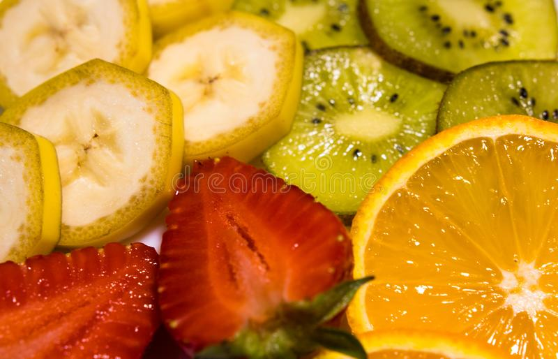W górę widoku na tropikalnych owoc: banan, kiwi, pomarańcze i truskawki, zdjęcie stock