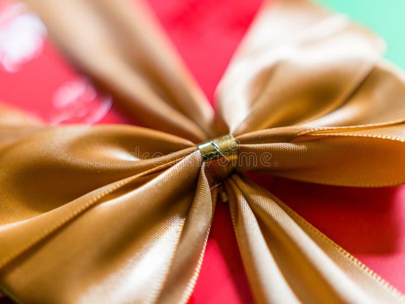 W górę widoku złocisty faborek lub łęk na czerwonym prezenta pudełku obrazy royalty free