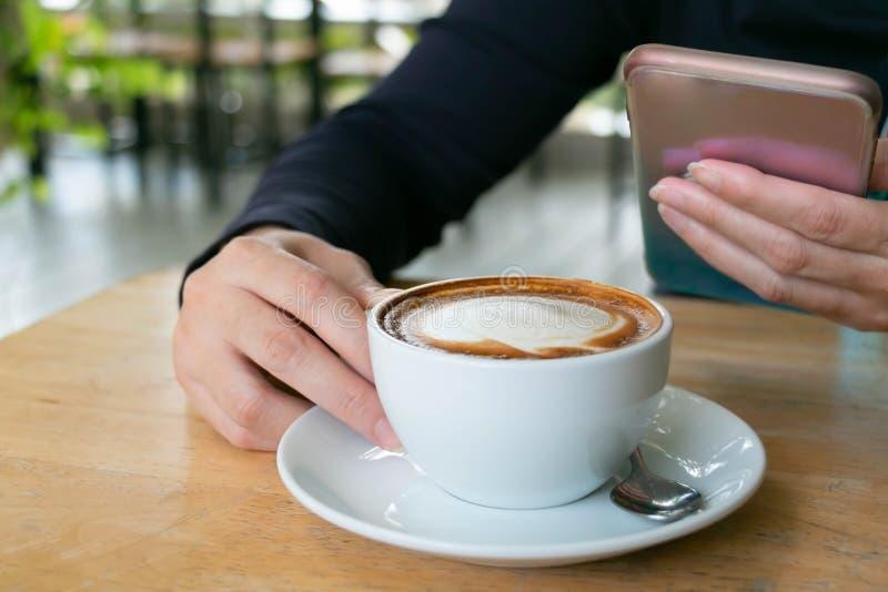 W górę wizerunku kobieta bierze czas przy sklepem z kawą z filiżanką gorący latte i jej telefon komórkowy zdjęcia stock
