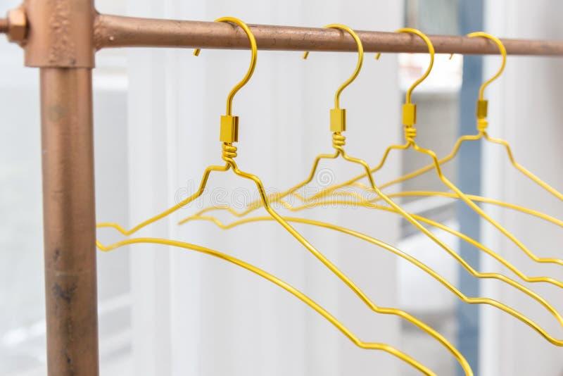 W górę złotego metalu odzieżowego wieszaka na miedzianym clothesline z białym zasłony tłem zdjęcia royalty free