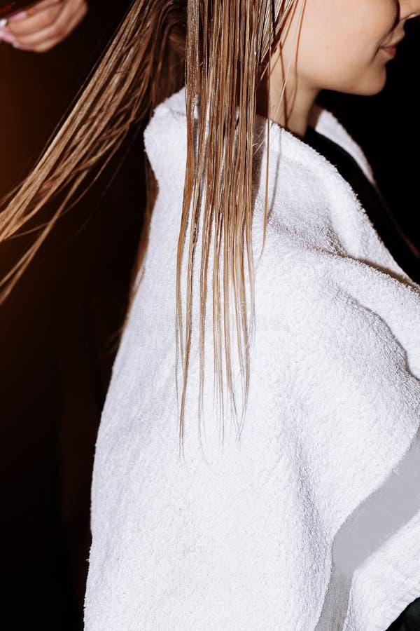 W g?r? fryzjer kobiety robi fryzurze klient z d?ugim blondynka w?osy zdjęcie royalty free
