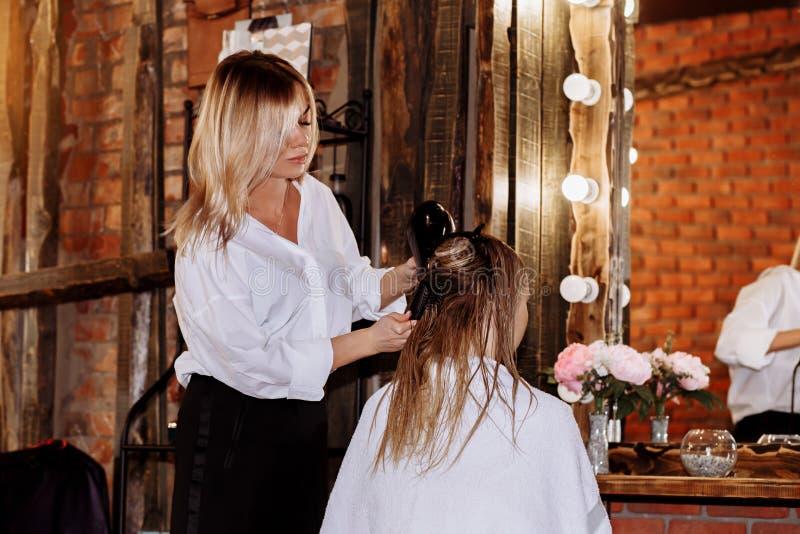 W g?r? fryzjer kobiety robi fryzurze klient z d?ugim blondynka w?osy obrazy royalty free