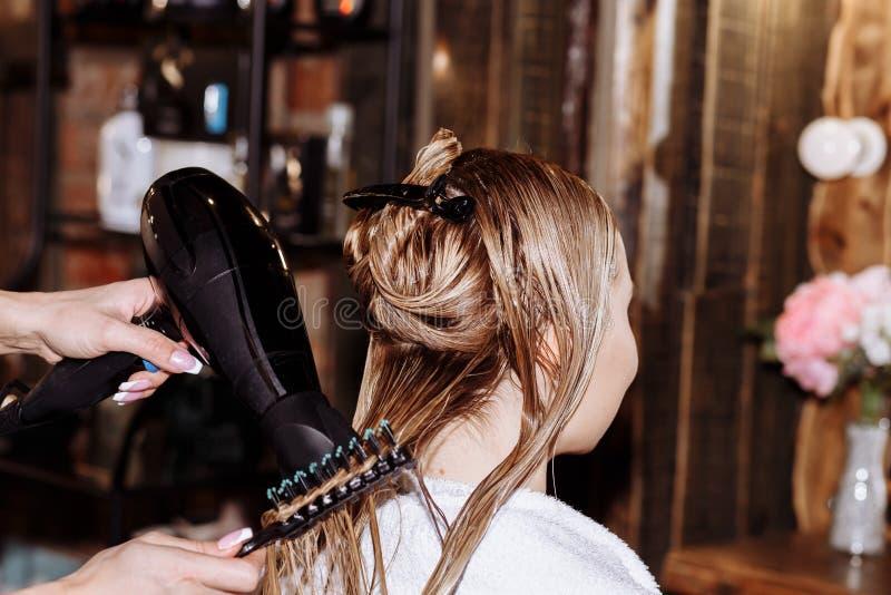 W g?r? fryzjer kobiety robi fryzurze klient z d?ugim blondynka w?osy fotografia royalty free