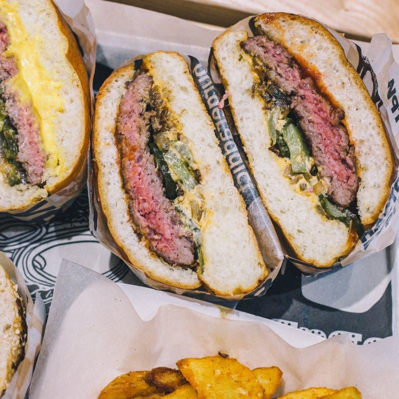 W g?r? r?ni?tych mi?snych hamburger?w i francuz?w d?oniak?w na tacy w kawiarni fotografia stock