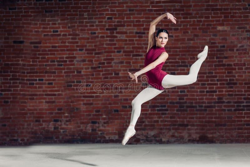 W jaskrawym białym studiu Młody tancerz wykonuje skok w powietrzu obraz stock