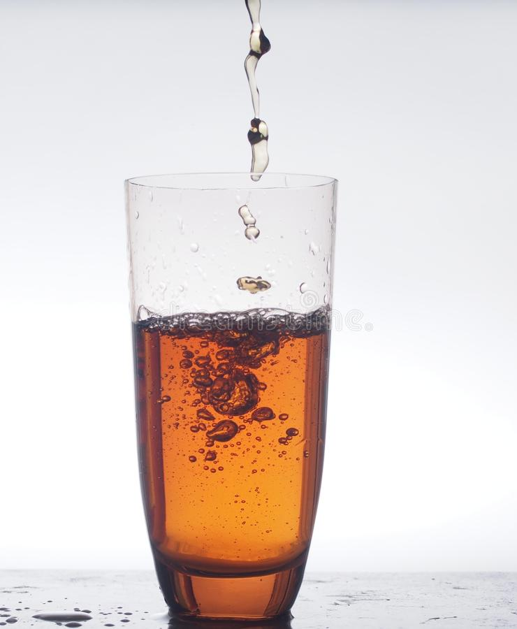 W jasnym szklanym strumieniu nalewający napój Fotografia na białym backgroun zdjęcia royalty free