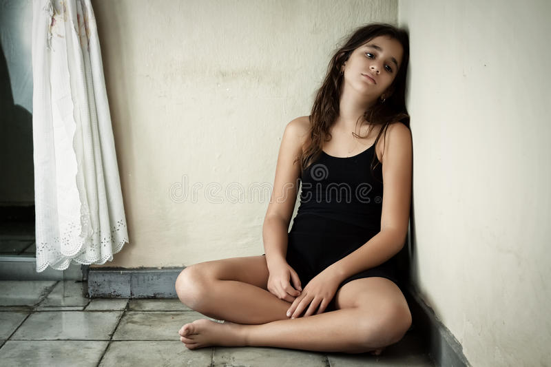 W kącie dziewczyny smutny i osamotniony łaciński obsiadanie zdjęcia stock