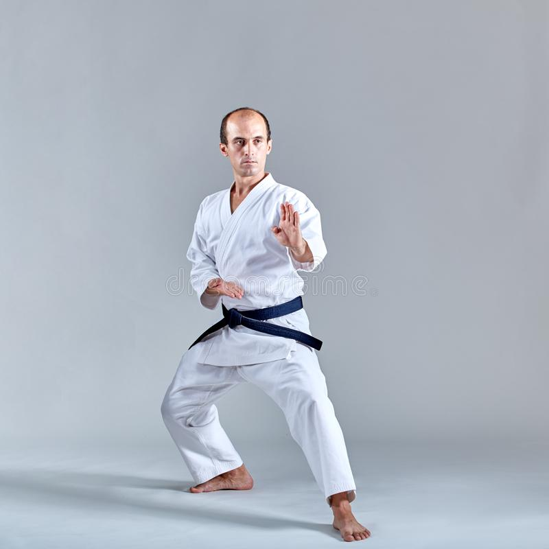 W karate stojaku, dorosła atleta trenuje formalnego karate ćwiczenie obrazy stock