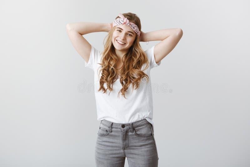 W końcu wydawać czas dla ja może Zrelaksowany atrakcyjny żeński uczeń w modnej kapitałce i przypadkowej koszulce trzyma, zdjęcia stock