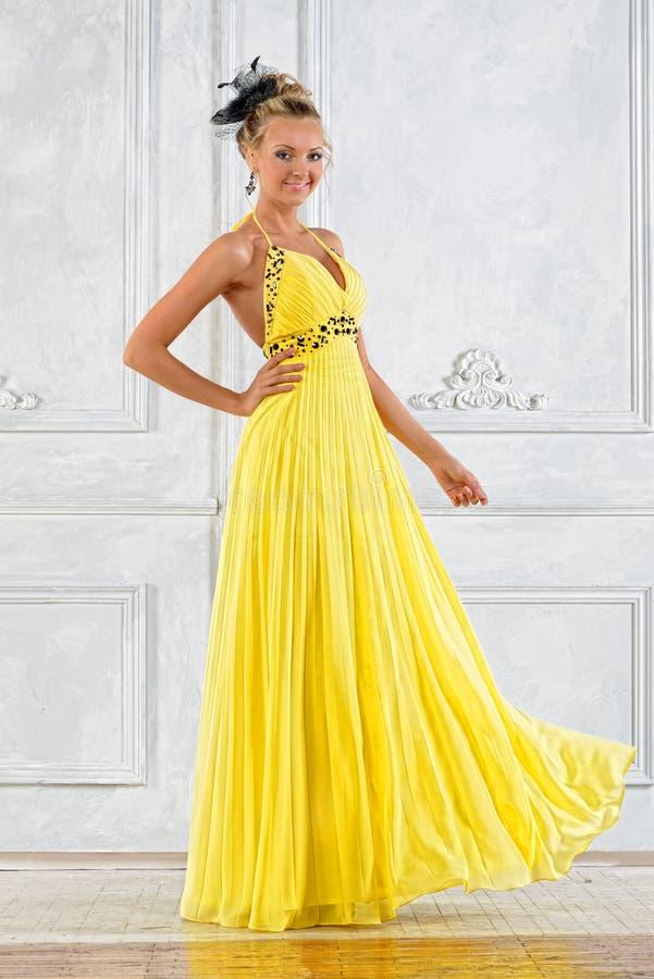W kolor żółty długiej sukni piękna kobieta. zdjęcie royalty free