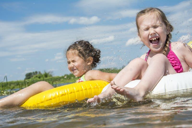 W lecie na rzecznych dwa dziewczynach na nadmuchiwanych okręgach obraz royalty free