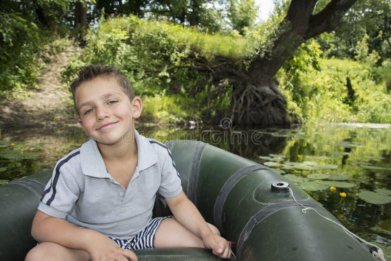 W lecie na rzeki chłopiec obsiadaniu w gumowej łodzi troszkę obrazy stock