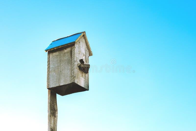 W lewym kącie rama na niebieskiego nieba tła birdhouse robić drewno zdjęcie stock