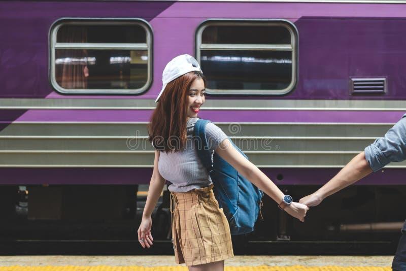 W miłości kobiety mienia młodym Azjatyckim chłopaku ręki podążają ona przy dworcem Romantyczny i podróży w wakacje pojęciu zdjęcia stock