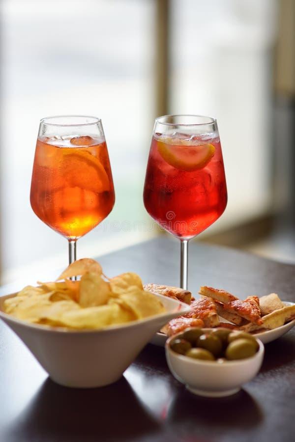W?oscy aperitives/aperitif: szk?o koktajlu iskrzasty wino z Aperol i zak?ska p??misek na stole zdjęcia stock