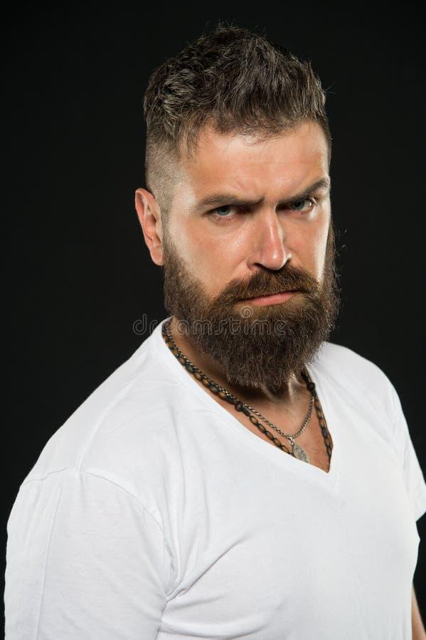 W?osiani projekt?w trendy Poważny modniś z długą brodą i elegancki włosy na czarnym tle Brodaty m??czyzna z nieogolon? twarz? zdjęcie royalty free