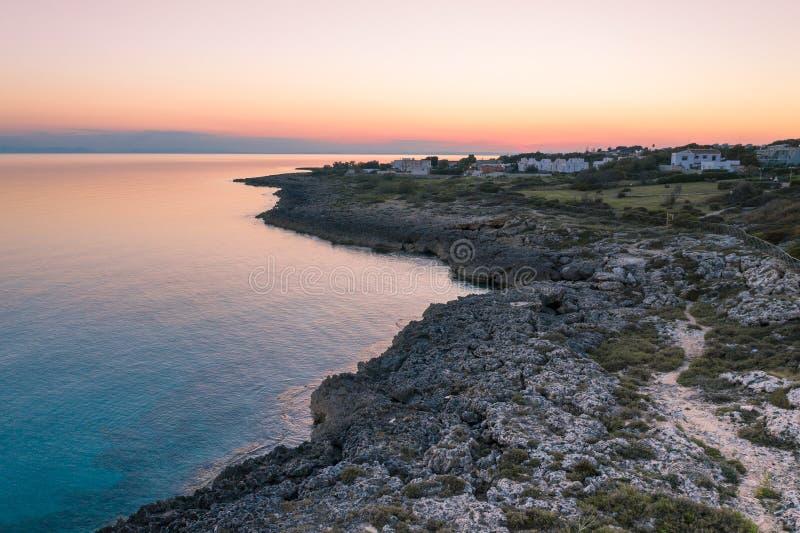W?oska linia brzegowa przy zmierzchem Widoku z lotu ptaka morze i skały spokojnej wody ciepły niebo fotografia stock