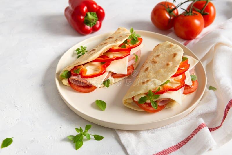 W?oski piadina romagnola flatbread z czerwonym pieprzem, pomidorami, prosciutto baleronem, serem i basilem na talerzu na bia?y dr obrazy stock