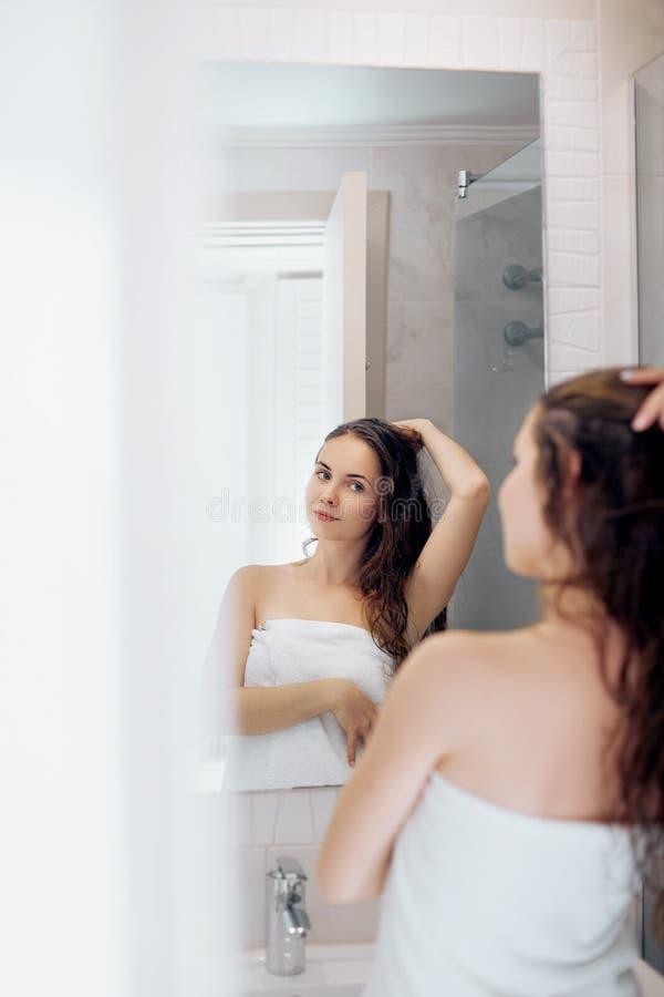 W?osy I cia?a opieka Kobiety macania mokry włosy i ono uśmiecha się podczas gdy patrzejący w lustrze Portret dziewczyna w łazienc obrazy stock