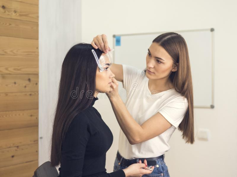 W piękno salonie robi makeup Mistrz i klient , piękno stylisty brwi kształtować obrazy stock