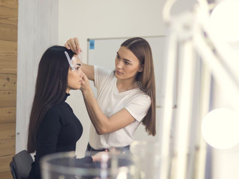 W piękno salonie robi makeup Mistrz i klient , piękno stylisty brwi kształtować zdjęcia stock