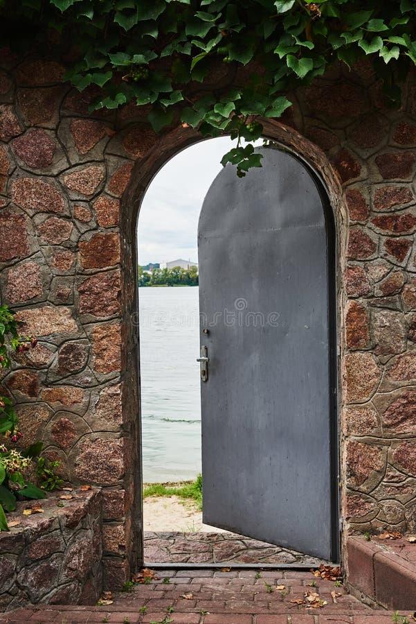 W pięknej kamiennej ścianie żelazny drzwi jest odchylony obrazy royalty free