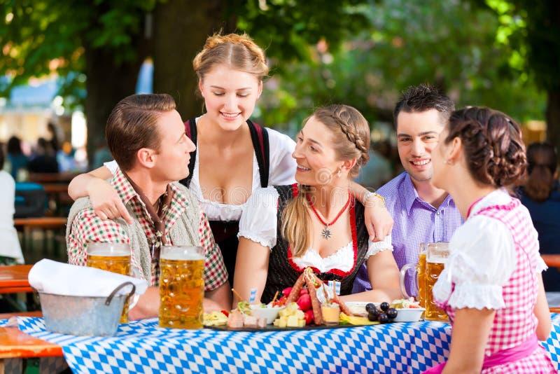 W piwo ogródzie - przyjaciele na stole z piwem fotografia stock