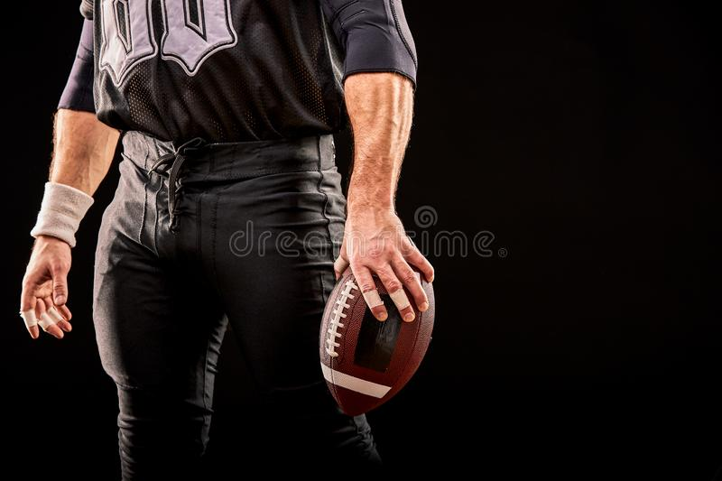 W połowie sekcja futbolu amerykańskiego gracz z piłką przeciw czerni, kopii przestrzeń zdjęcie stock