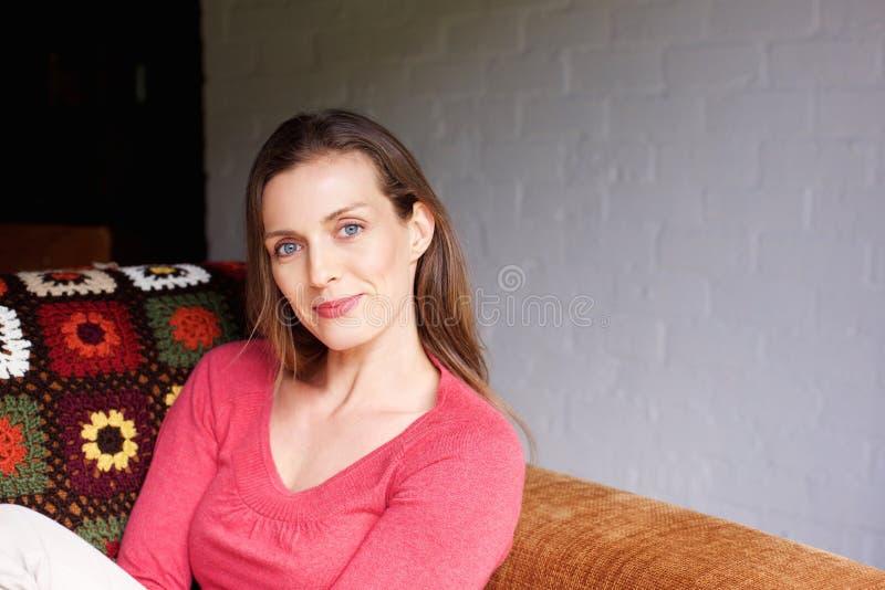 W połowie dorosła kobieta ono uśmiecha się w domu zdjęcie royalty free