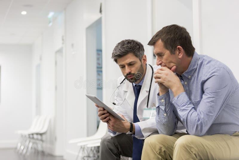 W połowie dorosłego doktorski wyjaśnia poważny pacjent nad cyfrową pastylką przy szpitalem zdjęcie royalty free