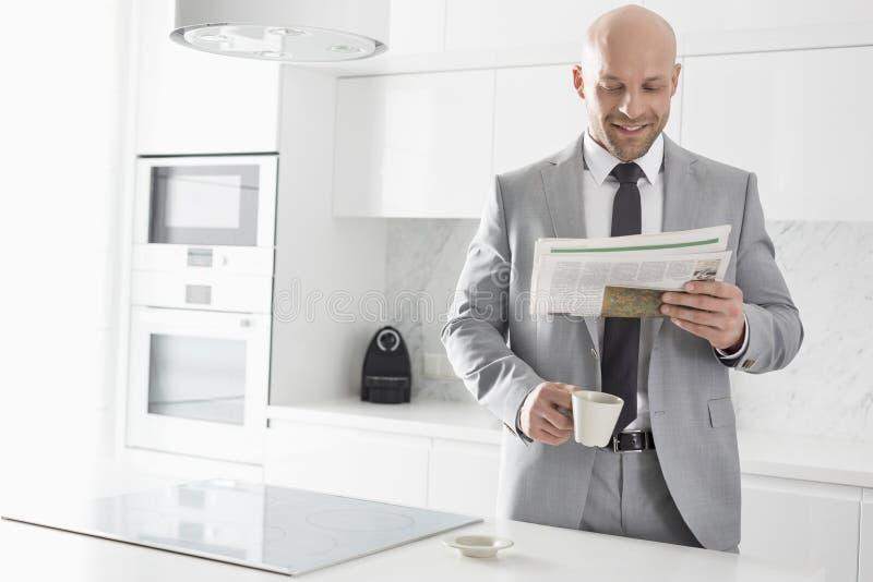 W połowie dorosły biznesmen ma kawę w kuchni podczas gdy czytający gazetę zdjęcie royalty free