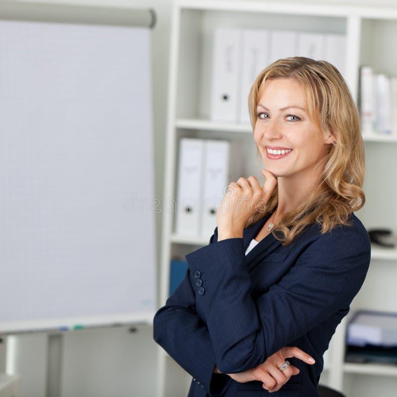 W połowie Dorosły bizneswoman ono Uśmiecha się W biurze obraz stock