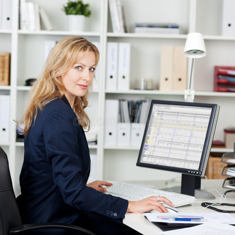 W połowie Dorosły bizneswoman Używa komputer Przy biurkiem obraz stock